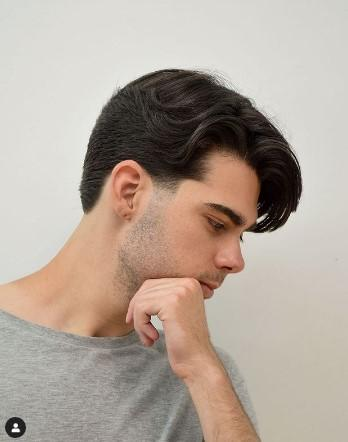 A person with his hand on his chin Description automatically generated with low confidence